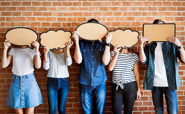 Line of people standing against a brick wall holding large thought bubbles over their faces.